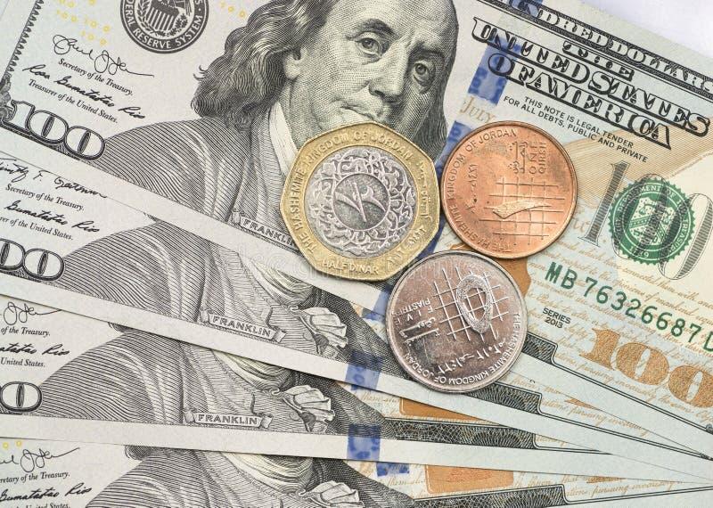 Pièce de dinar jordanien sur des billets d'un dollar image libre de droits