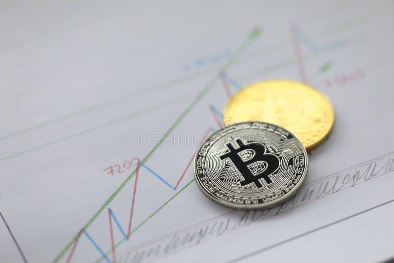 Pièce de monnaie argentée et d'or de mensonge de bitcoin sur des affaires image libre de droits