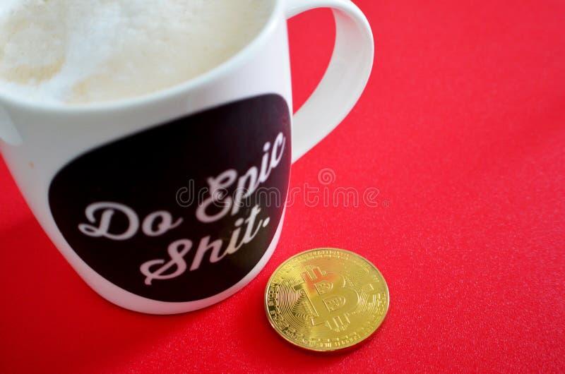 Pièce de monnaie de Bitcoin avec le slogan d'épopée de tasse de café photos stock