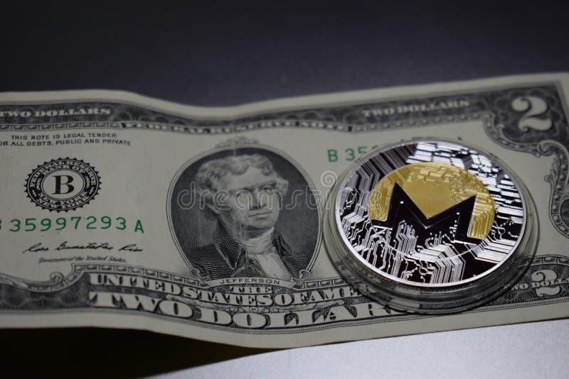 Pièce de monnaie de cryptocurrency de Monero sur deux dollars de billet de banque photographie stock libre de droits