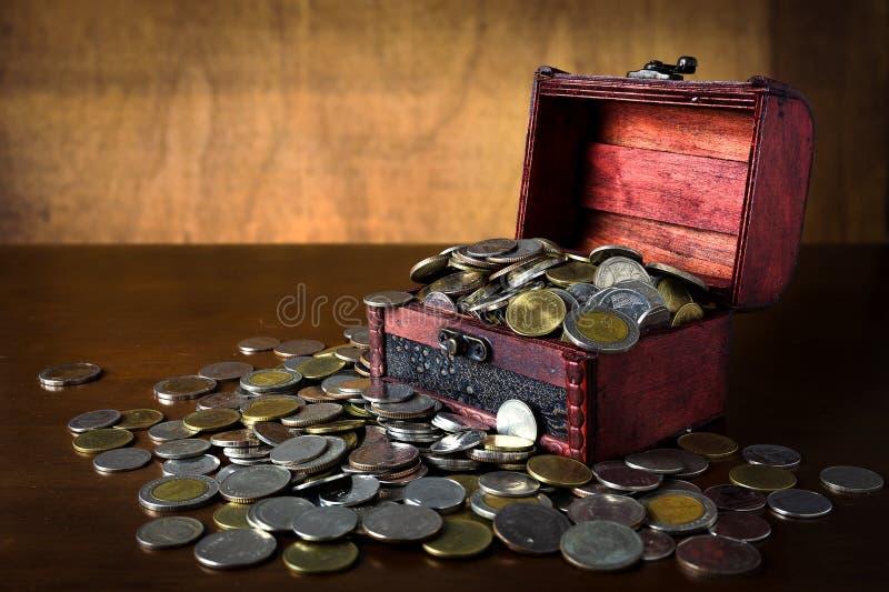 Pièce de monnaie d'économie dans la boîte en bois images stock
