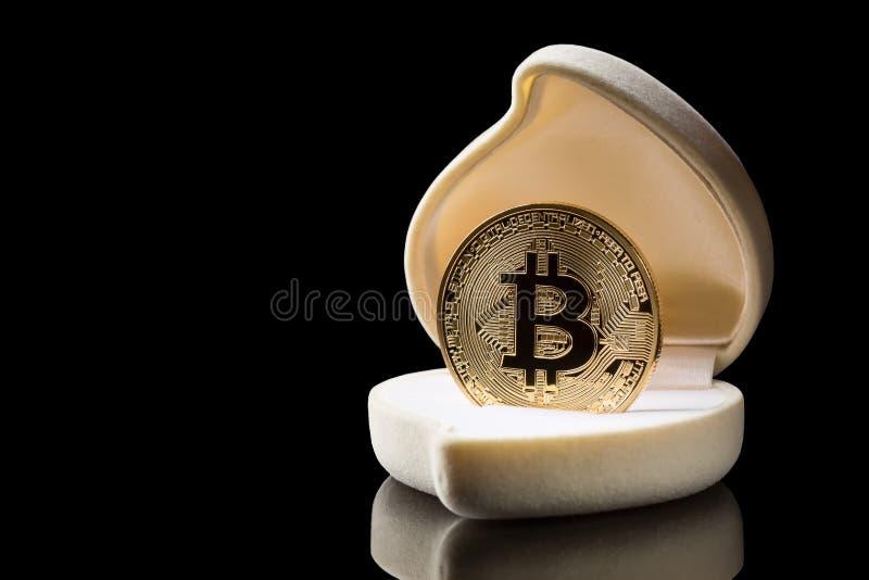 Pièce de monnaie d'or de Bitcoin dans la boîte d'anneau de mariage d'isolement sur le fond noir avec l'espace de réflexion et de  photo stock