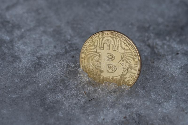Pièce de monnaie d'or de bitcoin en glace photographie stock libre de droits