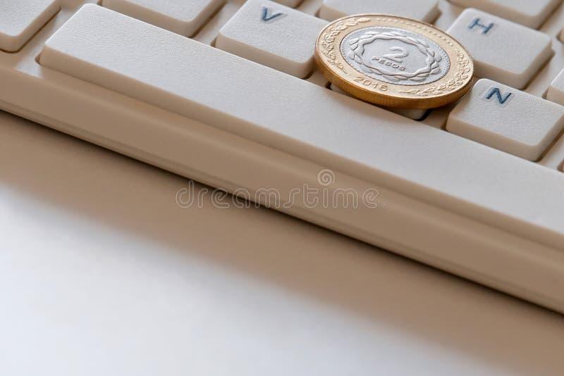 Pièce de monnaie dans deux pesos sur le plan rapproché de clavier d'ordinateur Affaires en ligne en Argentine Ventes internationa photos stock