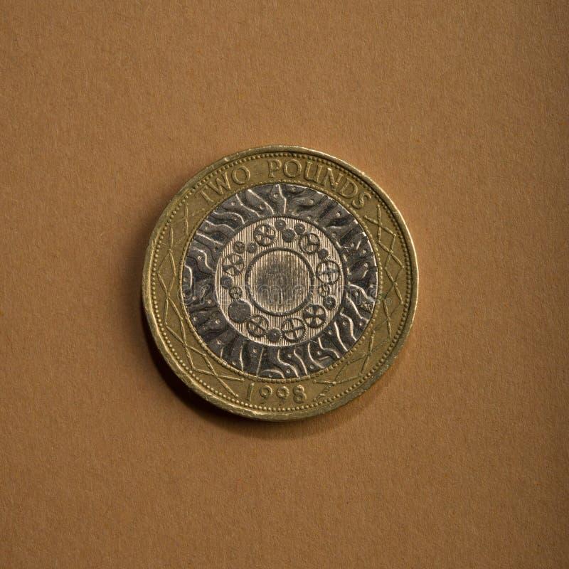 Pièce de monnaie de deux livres sur un fond brun photo stock