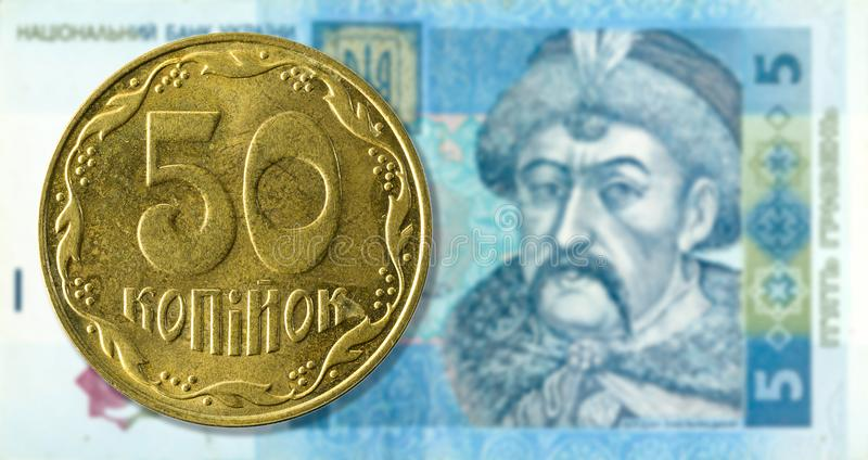 pièce de monnaie du kopiyka 50 contre la face de billet de banque de hryvnia de 5 Ukrainiens photos stock