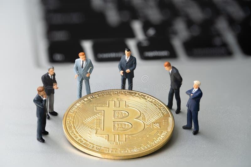 Pièce de monnaie et businessmans de Bitcoin BTC sur le carnet photos libres de droits