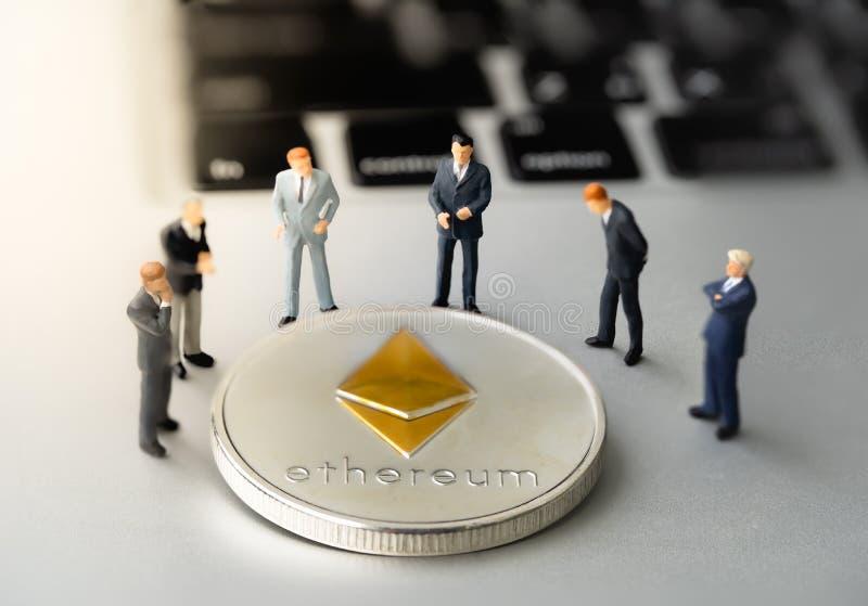 Pièce de monnaie et businessmans d'Ethereum ETH sur le carnet photos stock