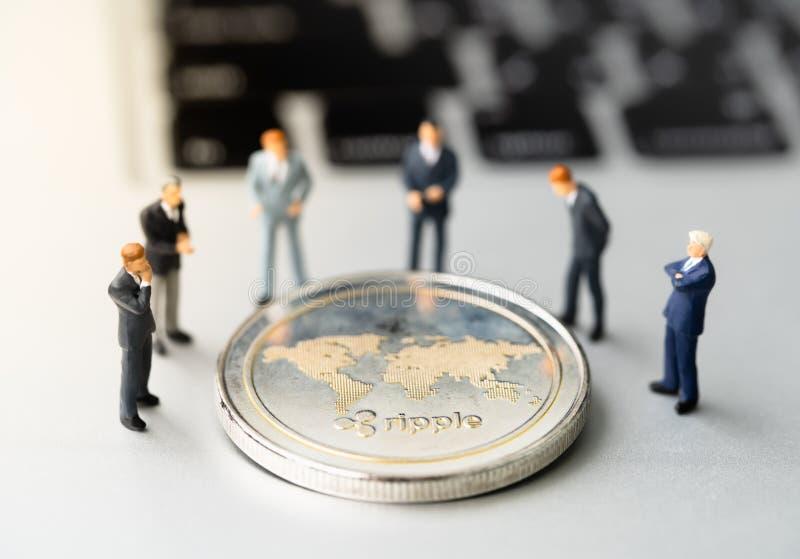 Pièce de monnaie et businessmans de l'ondulation XRP sur le carnet images stock