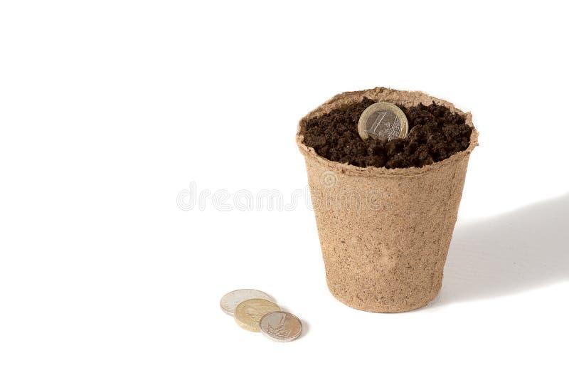 Pièce de monnaie et un pot de tourbe pour des jeunes plantes se situant ensemble, à une société rurale de production agricole d'i photos stock