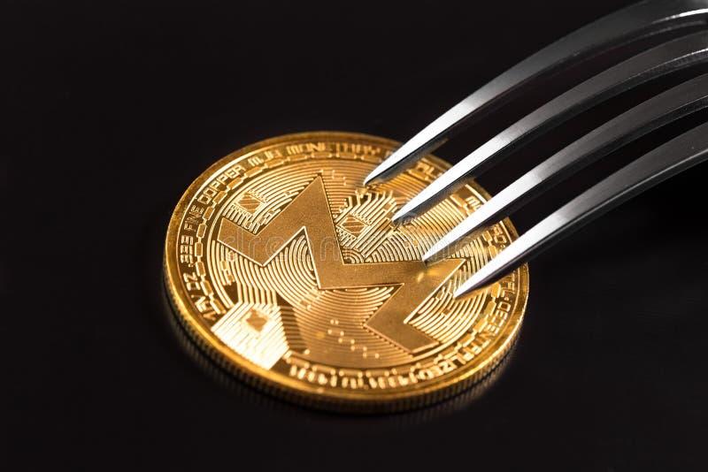 Pièce de monnaie de Monero sous la fourchette photo stock