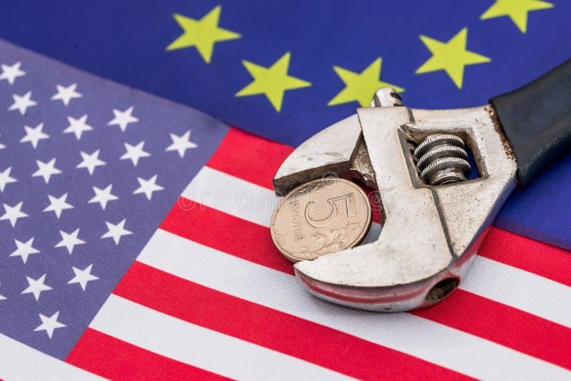 Pièce de monnaie de rouble dans l'étau sur le drapeau de l'Europe et de l'Amérique photo stock