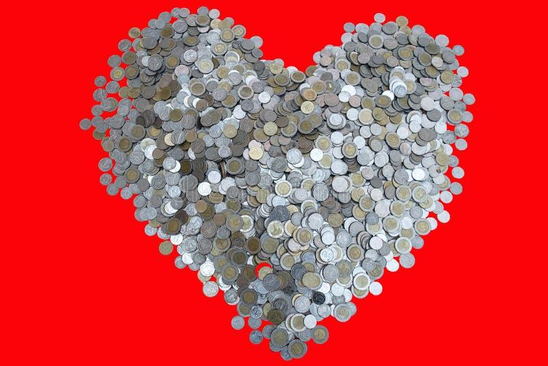 Pièce de monnaie de sorts de baht thaïlandais disposée dans la forme de coeur dessus avec la texture noire de fond, l'investissem images stock