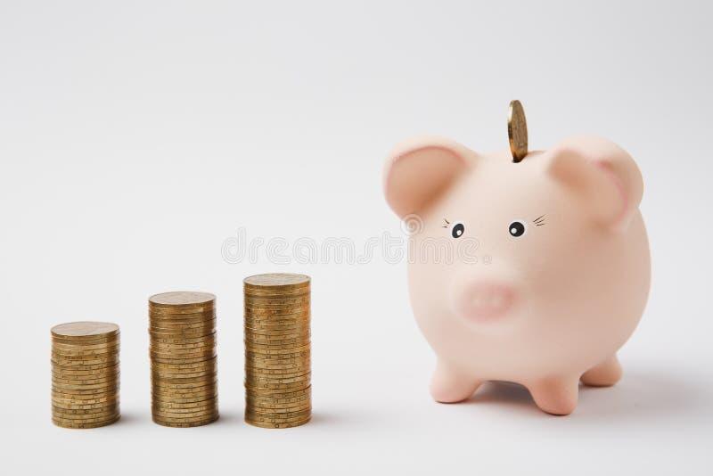 Pièce de monnaie tombant dans la banque porcine rose d'argent, piles de pièces de monnaie d'or d'isolement sur le fond blanc Accu image stock