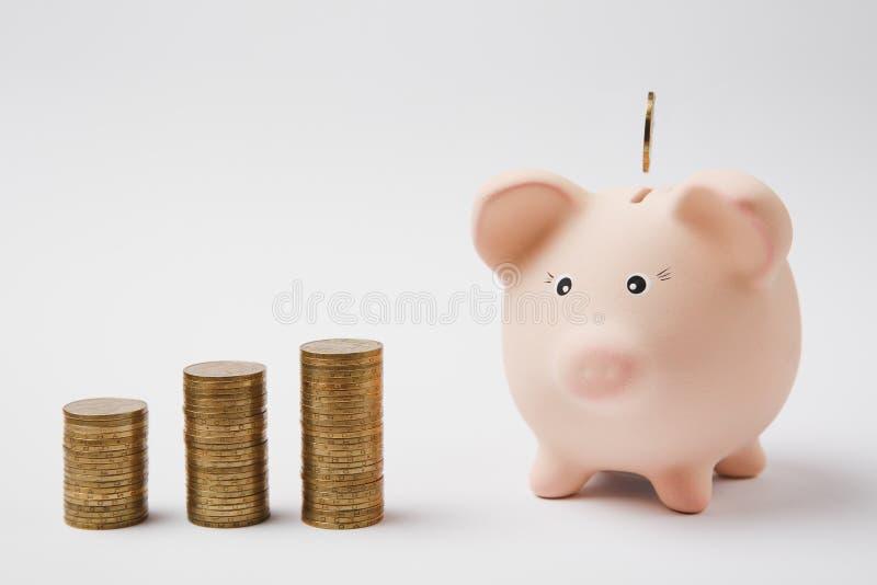 Pièce de monnaie tombant dans la banque porcine rose d'argent, piles de pièces de monnaie d'or d'isolement sur le fond blanc Accu photo stock