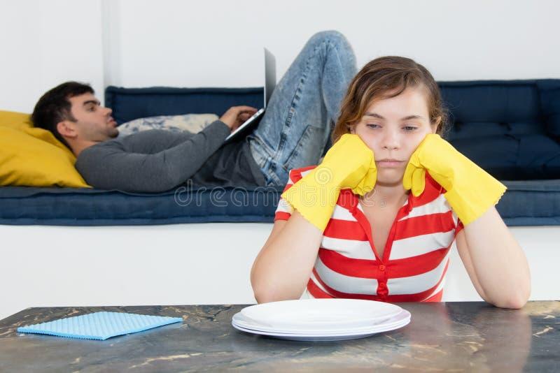 Pièce de nettoyage frustrante de femme au foyer avec le mari paresseux images libres de droits
