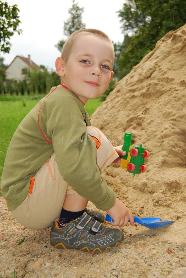 Pièce de petit garçon avec le sable photo stock