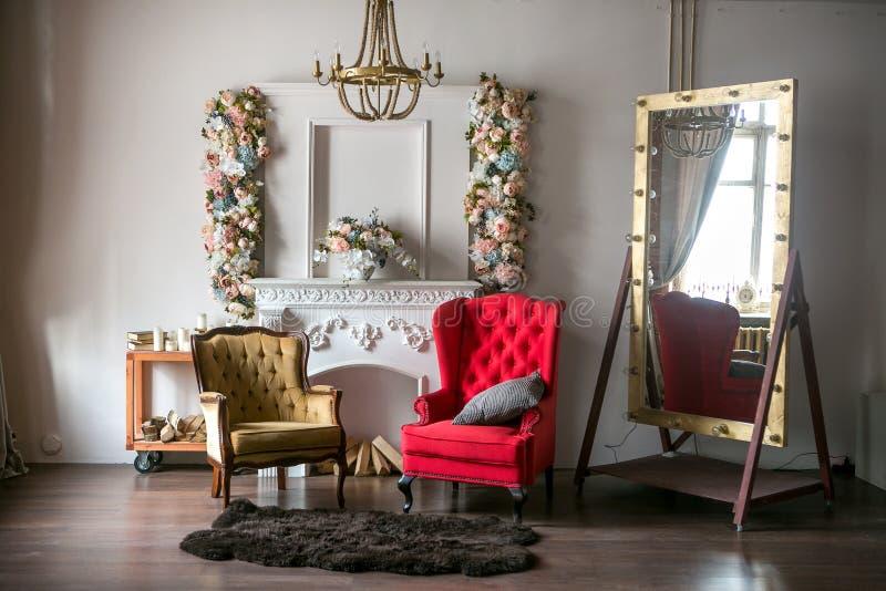 Pièce de style du grenier lumineuse avec un fauteuil rouge, un fauteuil brun, une cheminée blanche avec des fleurs, un grand miro image stock