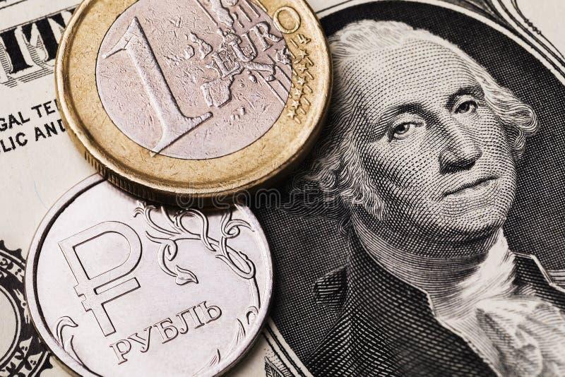 Pièce en euro et rouble russe sur fond de billet de banque en dollars, gros plan images stock