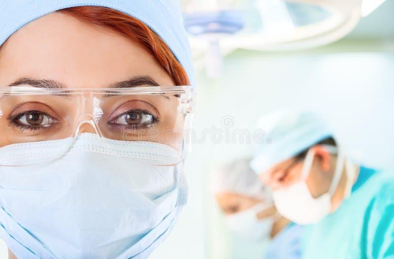 Pièce en fonction de jeune docteur féminin avec son équipe images stock