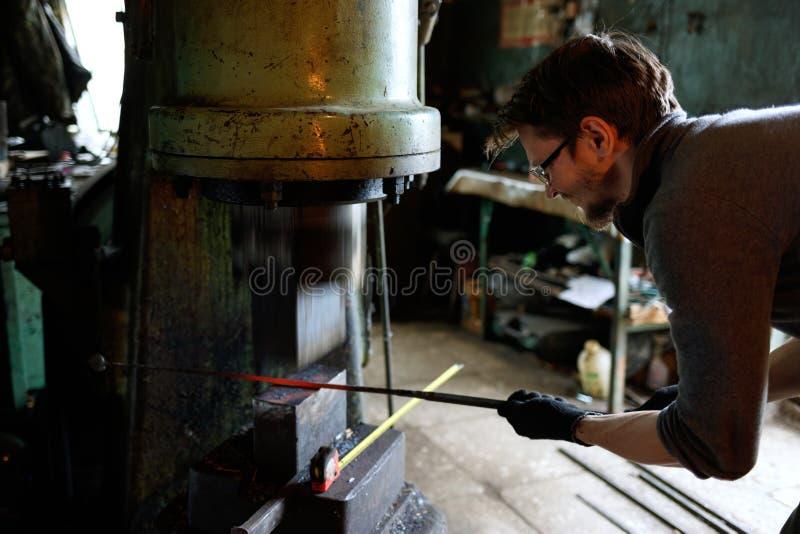 Pièce forgéee de forgeron à l'aide de marteau pneumatique image stock