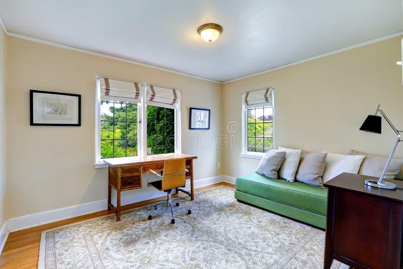 Pièce lumineuse de bureau avec le divan vert image stock
