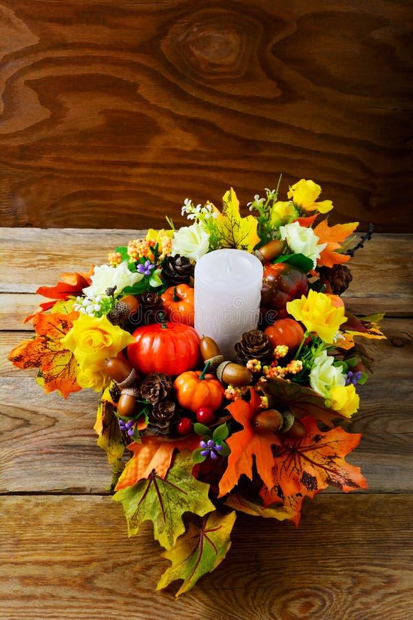 Pièce maîtresse de thanksgiving avec la bougie et les feuilles artificielles de chute photographie stock libre de droits