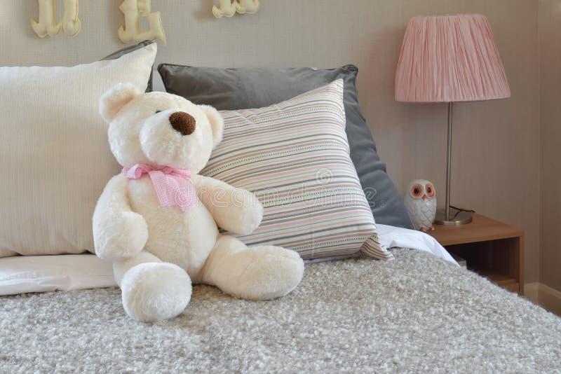 Pièce moderne d'enfants avec la poupée et les oreillers sur le lit photos stock