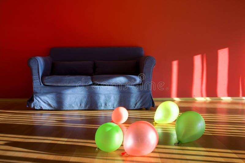 Pièce rouge avec le sofa bleu avec des ballons photo libre de droits