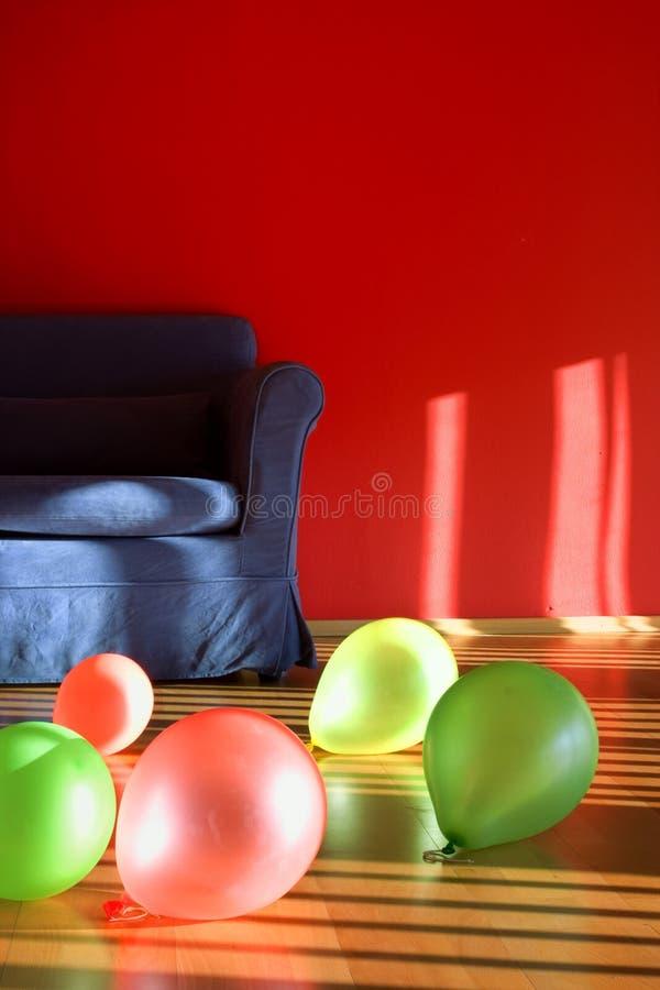 Pièce rouge avec le sofa bleu avec des ballons photo stock