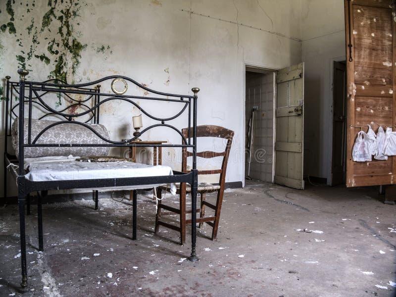 Pièce ruinée avec le lit et matelas négligé dans la maison ruineuse illustration libre de droits