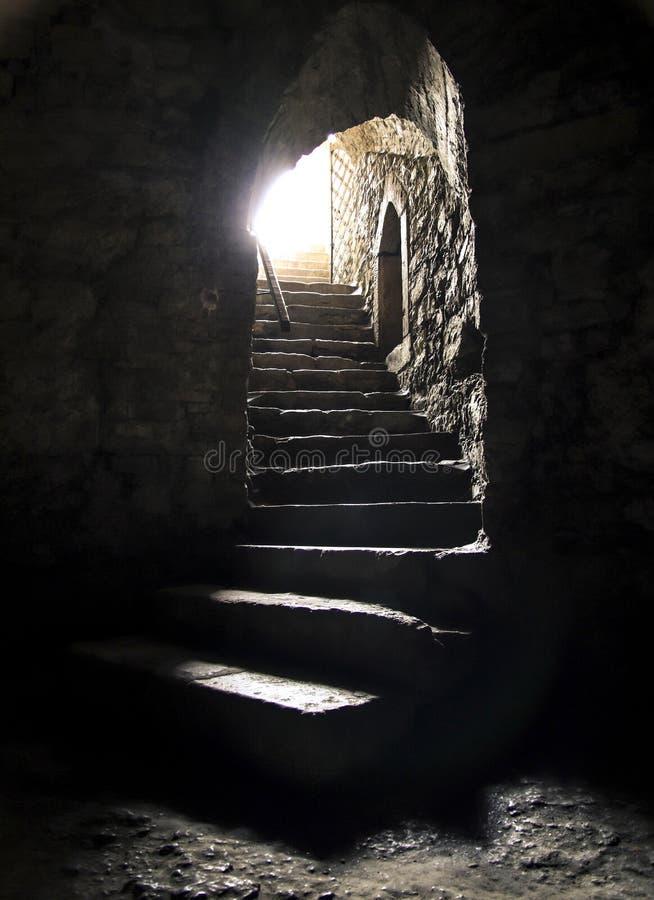 Pièce souterraine avec la lumière lumineuse brillant à l'extrémité de l'escalier Je vois léger à la fin du concept de tunnel images stock