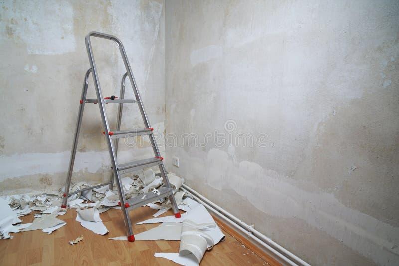 Pièce vide avec l'échelle de murs nus et vieilles chutes de papier peint sur le plancher pendant la remise à neuf des peintures a images stock