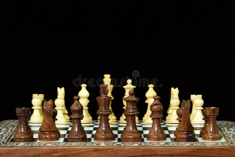 Pièces d'échecs et panneau sur le noir photographie stock