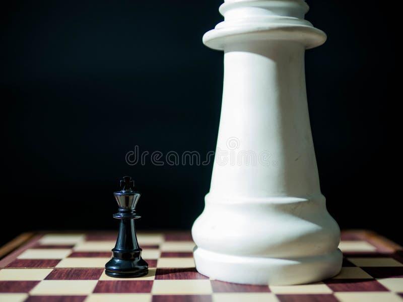 Pièces d'échecs noires avec les grands échecs blancs, concept d'affaires d'échecs images libres de droits
