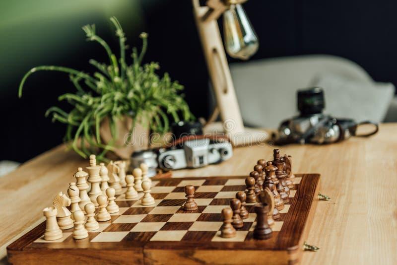 Pièces d'échecs sur l'échiquier prêt à commencer le jeu avec des appareils-photo de vintage photos libres de droits