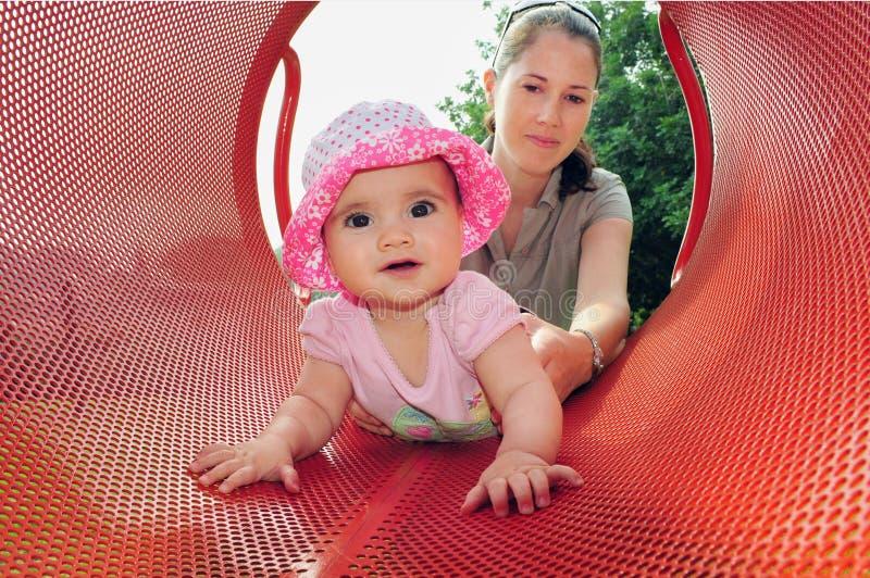 Pièces de bébé avec la momie dans la cour de jeu photographie stock libre de droits