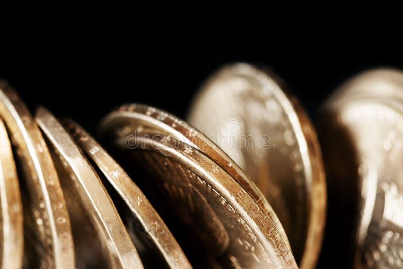 Pièces de monnaie au-dessus de noir photos stock