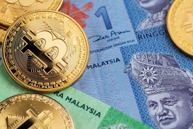 Pièces de monnaie de Bitcoin Cryptocurrency sur des billets de banque de devise de ringgit de la Malaisie photographie stock libre de droits