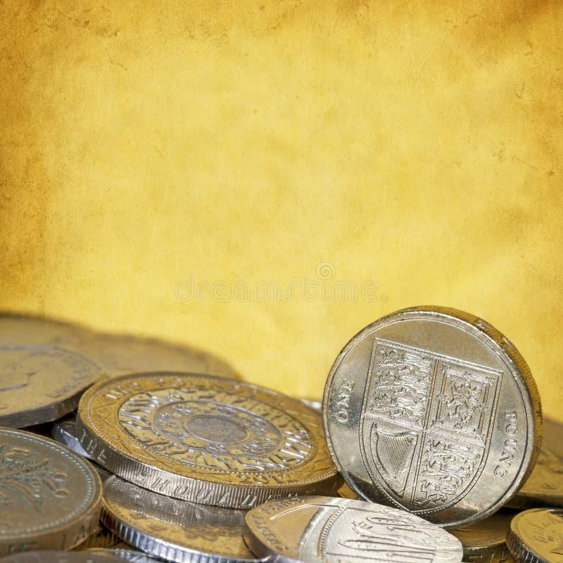 Pièces de monnaie britanniques avec Copyspace jaune grunge photographie stock libre de droits