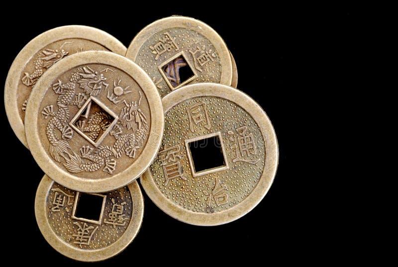 Pièces de monnaie chinoises de chance sur le noir images stock