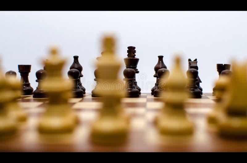 Pièces de monnaie d'échecs se tenant vis-à-vis l'un l'autre images stock