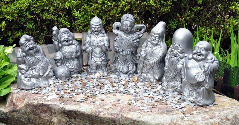Pièces de monnaie d'argent et sept statues chanceuses de dieux à Daisho-dans le temple, île Japon de Miyajima image stock