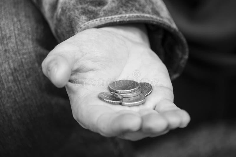 pièces de monnaie d'euros à disposition du pauvre homme s'asseyant dans la rue photographie stock