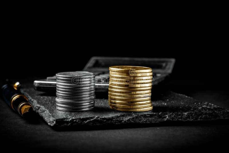 Pièces de monnaie d'un stylo-plume, de calculatrice, argentées et d'or Concept d'affaires, de finances ou d'investissement images stock