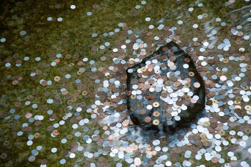 Pièces de monnaie dans un puits de souhait photos stock