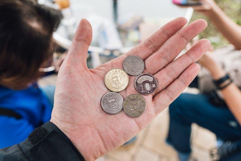 10 pièces de monnaie des dollars de nouveau Taïwan en versions de Sun Yat-sen et de Chiang Kai-shek dans la paume de main gauche photos stock