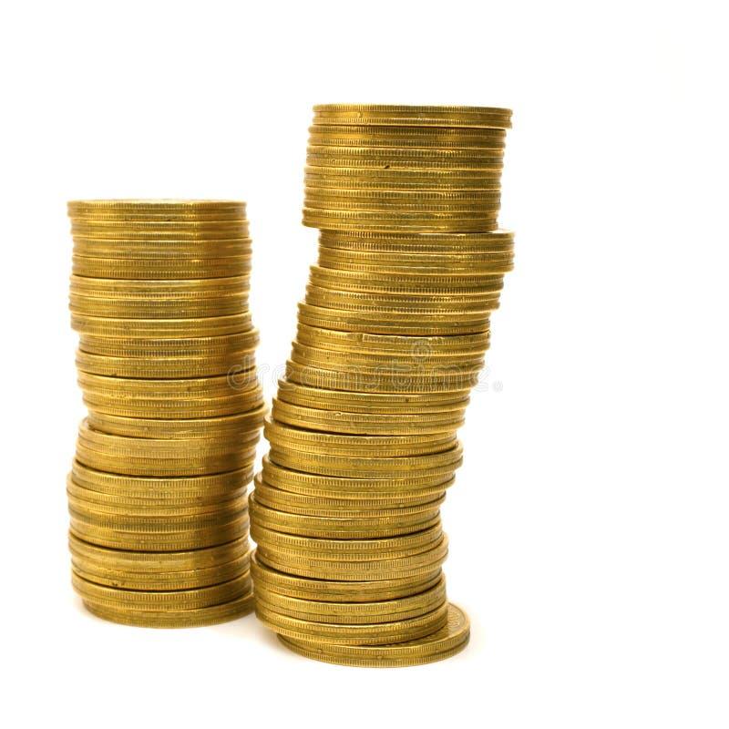 Pièces de monnaie empilées d'isolement sur le blanc images libres de droits