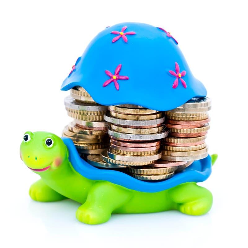 Pièces de monnaie empilées sur la tortue images libres de droits