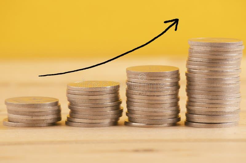 Pièces de monnaie empilées sur le fond jaune pour le concept de croissance d'affaires image stock